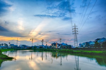 Sunset in urban areas, featuring transmission towers, ponds that make beautiful reflection, crane, rays of light and many houses