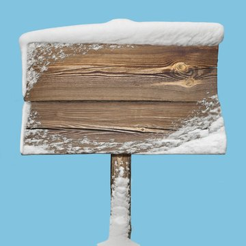 Wooden sign with snow isolated on blue