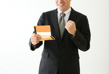通帳を見てガッツポーズする男性