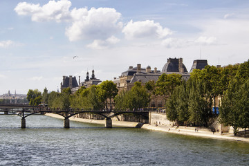 View of Seine river, Pont des Arts, trees and buildings in Paris.