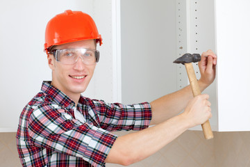 repairman in a helmet with a hammer