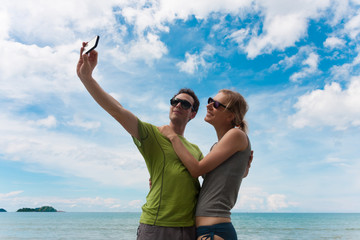 Happy couple makes selfie on sea beach. Family vacation concept