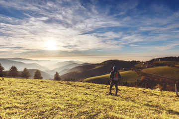 Man backpacker hiking in mountains in autumn looking at beautiful landscape with mountains forest and a village at sunset. Wall mural