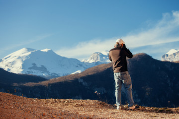 handsome man travel in winter mountains with camera