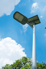 Led spotlight with solar power in street garden and blue sky background.
