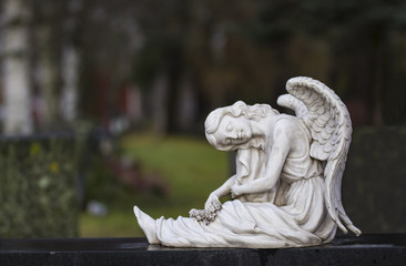 Angel statue sitting on a gravestone in the cemetery