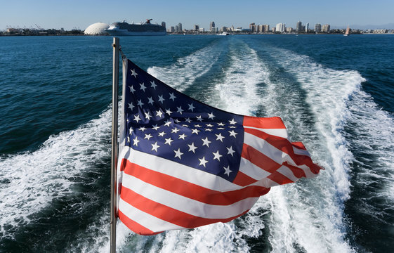 The American flag flies on the back of the boat. View from the boat on the American flag and the city