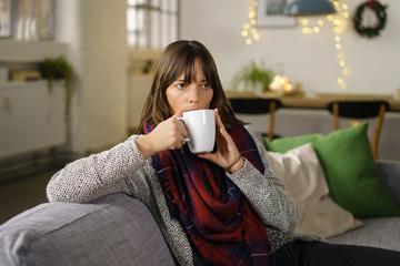 nachdenkliche frau sitzt auf dem sofa mit einer tasse tee