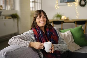 entspannte frau sitzt zuhause auf dem sofa mit einer tasse tee