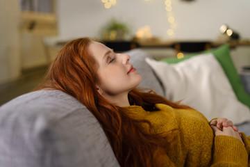 frau liegt entspannt zu hause auf dem sofa