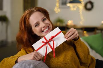 attraktive frau freut sich über einen gutschein zu weihnachten