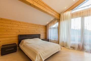 Bedroom with bed, bedside tables, vaulted ceiling, windows with window coverings
