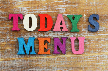 Today's menu written with colorful letters on rustic wooden surface