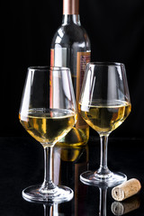 Two glasses of white wine and the bottle on black  background