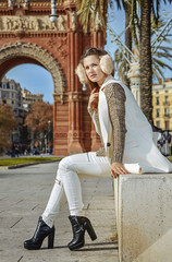 woman looking into distance while sitting on parapet, Barcelona