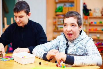 happy kids with disability develop their fine motor skills at rehabilitation center for kids with special needs