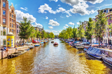 NETHERLANDS, AMSTERDAM - AUGUST 15, 2011: The view from the bridge over the canal in Amsterdam, cars, bikes and tourists who enjoy.