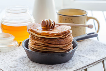 pancakes in a cast iron skillet with honey