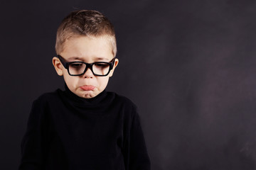 Portrait of sad child in pullover and glasses