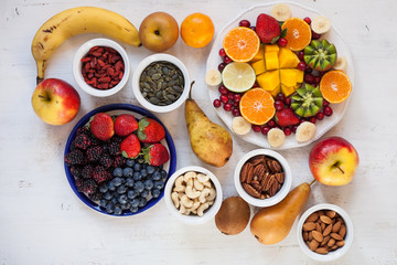 Vegan breakfast: variety of fruits, nuts and berries on the white wooden table, selective focus, top view