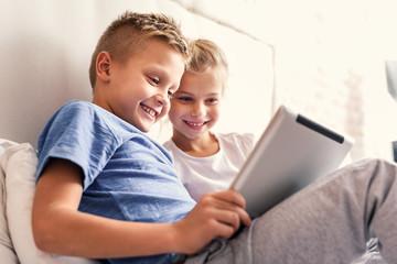 Children enjoying digital gadget in bedroom