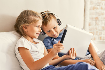 Cute brother and sister enjoying tablet at home