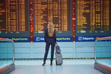 Young woman in international airport looking at the flight information board, checking her flight Wall mural