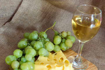 still life with glass of white wine, cheese and grapes on wooden background