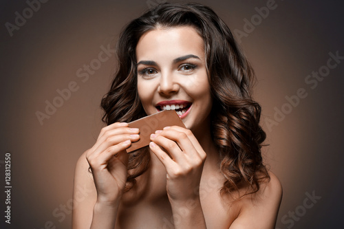 Beautiful Girl With Chocolate On Brown Background Stock Photo And