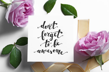 """Inscription """"DON'T FORGET TO BE AWESOME"""" written on paper with flowers and ribbon on white background"""
