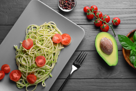 Spaghetti with cherry tomatoes and avocado sauce on wooden table, top view