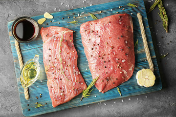 Tasty steaks with marinade ingredients on blue cutting board, closeup