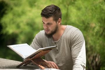 Muslim Man Is Reading The Koran In Park