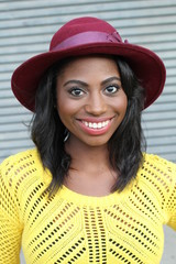 Funky style beauty. Portrait of beautiful young African woman in funky hat smiling while standing against gray urban background
