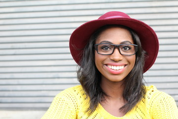 Funky style beauty. Portrait of beautiful young African woman in glasses and funky hat smiling while standing against gray urban background