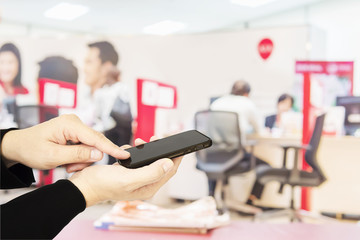 A man is using telephone over colorful blurred bokeh light in office and people background