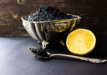 bowl with black caviar with a lemon and a silver spoon. black background