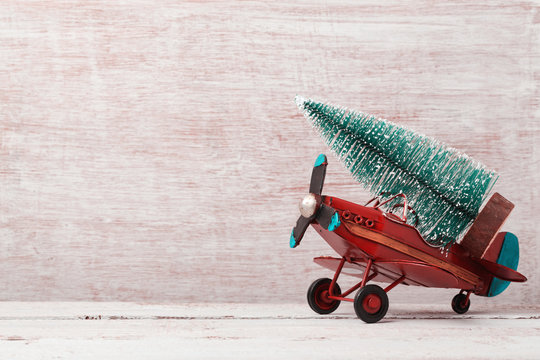 Christmas background with rustic vintage airplane toy and pine tree
