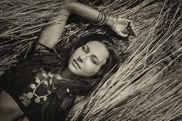 Beautiful young boho woman lying on grass