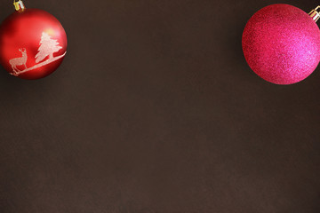 Christmas red and pink ball on dark wooden table. Top view.