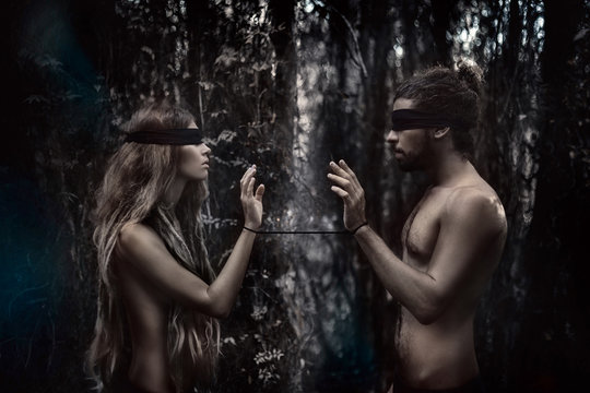 atrractive young man and woman with eyes closed. lost in forest