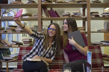 Girls taking selfie by phone in the library