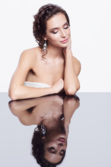 Portrait of young beautiful brunette woman sitting at mirror table