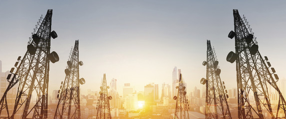 Silhouette, telecommunication towers with TV antennas and satellite dish in sunset, with double exposure city in sunrise background Wall mural