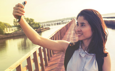 smiling young woman take a selfie photo at wooden bridge by the