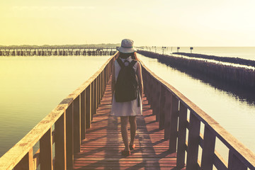 young woman walking on wooden bridge extended into the sea, chal
