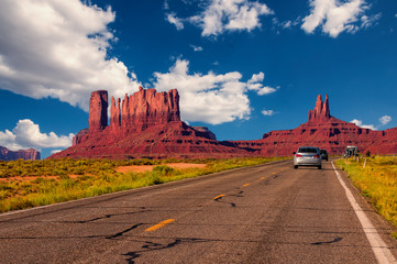 Highway in Monument Valley, Utah / Arizona, USA - Picture with road and cars driving towards the hills. Photo made during a road trip throughout the western states.