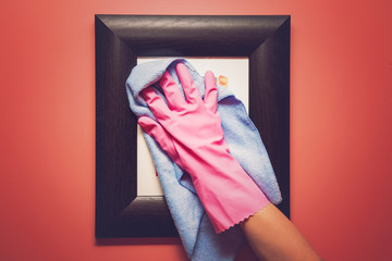 Hand in pink protective glove wiping picture or photo frame on the wall from dust with rag. Early spring cleaning or regular clean up. Maid cleans house.
