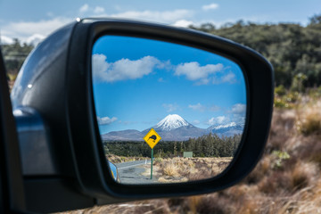 Foto auf Gartenposter Reflexion Road to Tongariro National Park with Kiwi sign reflected in the rear mirror, New Zealand