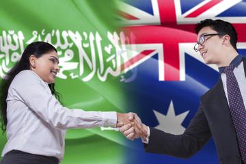Australian person shaking hands with Arabian woman